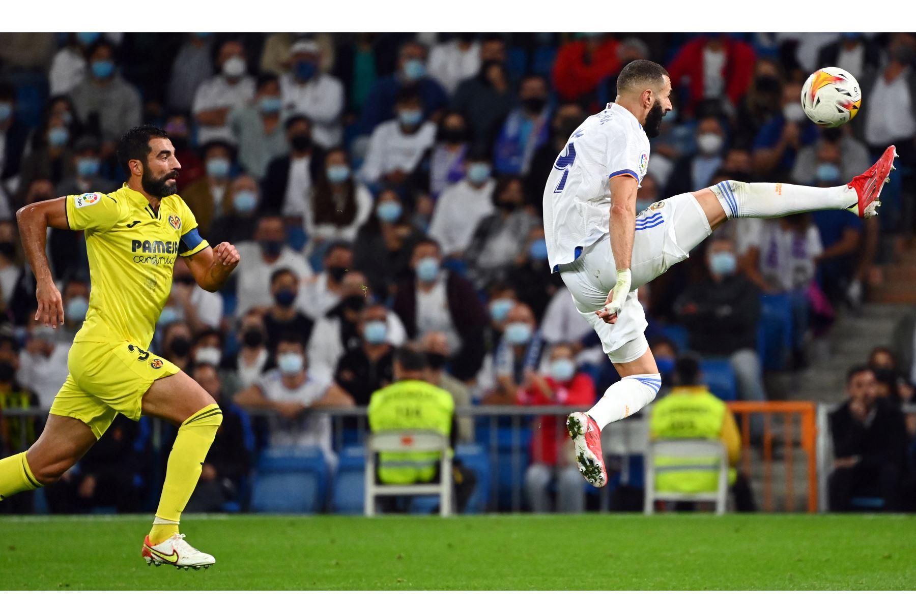 El delantero francés del Real Madrid Karim Benzema patea el balón cuando el defensor español del Villarreal Raúl Albiol se acerca durante el partido de fútbol de la Liga española entre el Real Madrid y el Villarreal. Foto: AFP