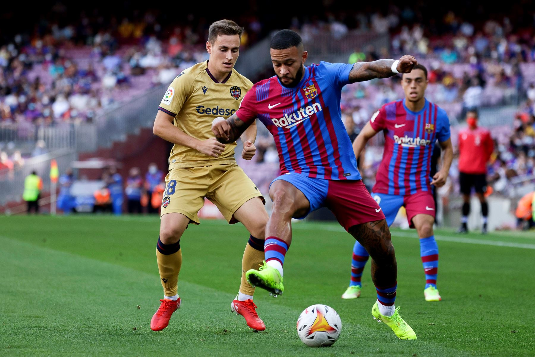 El delantero holandés del Barcelona Memphis Depay disputa el balón ante el extremo del Levante Jorge De Frutos durante el partido de la séptima jornada de LaLiga Santander, en el estadio Camp Nou. Foto: EFE