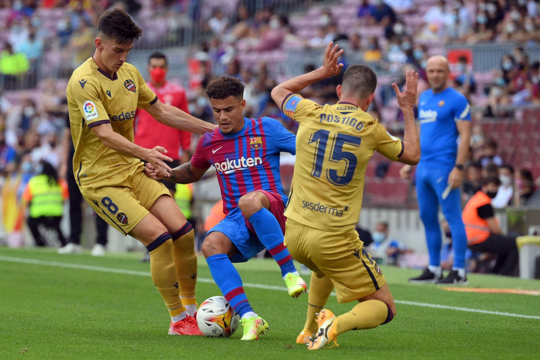 El centrocampista brasileño del Barcelona Philippe Coutinho es desafiado por el centrocampista español Pepelu y el defensa Sergio Postigo del Levante durante el partido de la Liga española. Foto: AFP