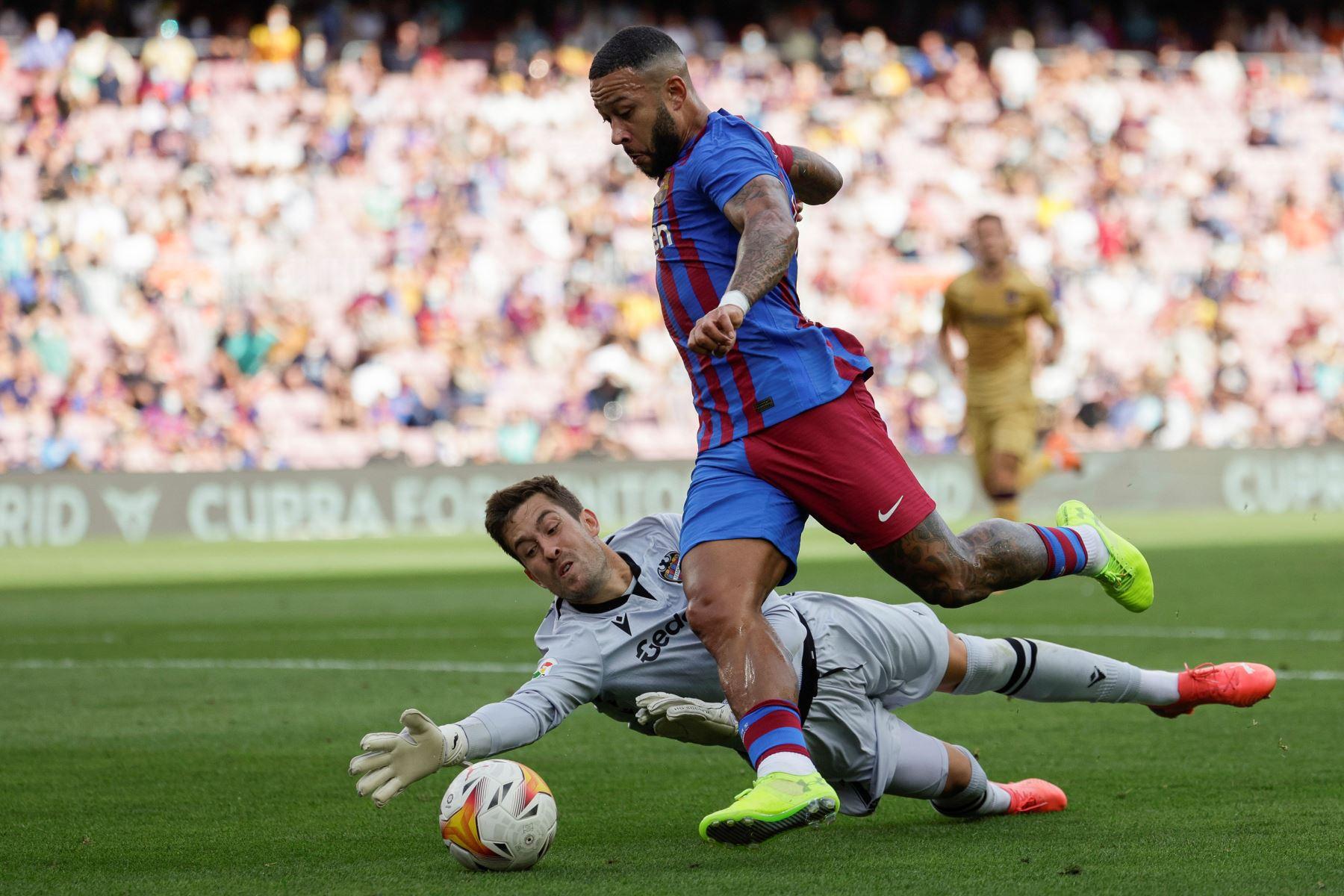 El delantero holandés del Barcelona Memphis Depay trata de marcar ante el portero del Levante Aitor Fernández durante el partido por la séptima jornada de LaLiga Santander, en el estadio Camp Nou. Foto: EFE
