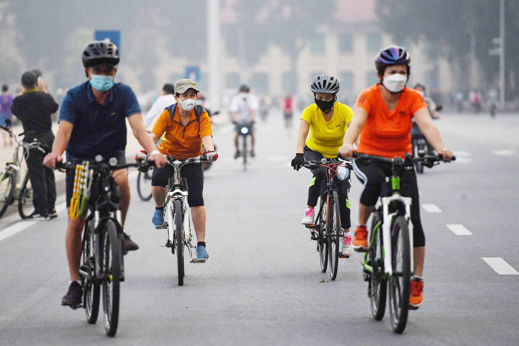 Las personas andan en bicicleta a lo largo de una calle en Hanoi , luego de que las autoridades de la ciudad permitieran las actividades deportivas al aire libre luego de la flexibilización de las restricciones del coronavirus. Foto: AFP