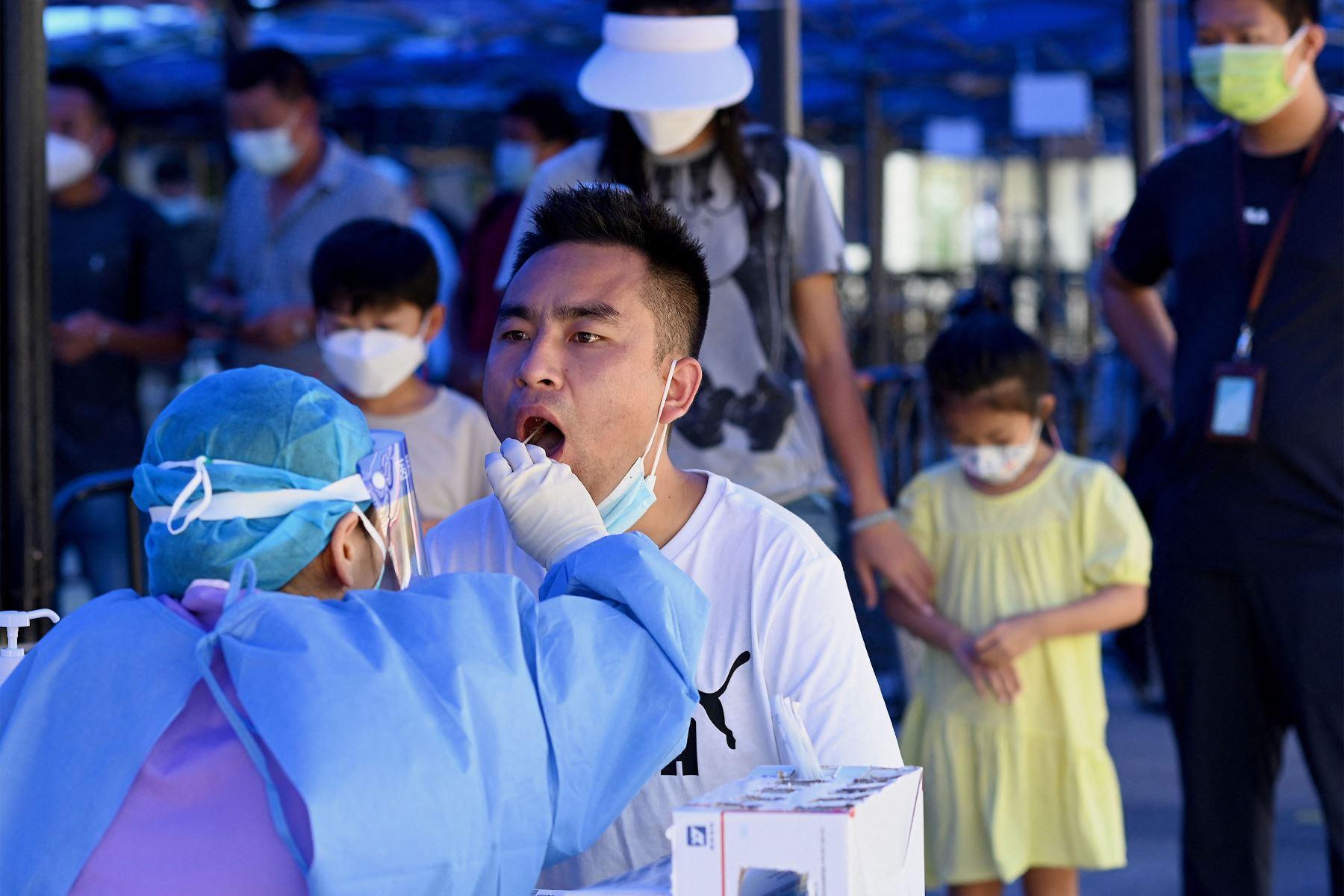 Un trabajador de la salud toma una muestra de ácido nucleico para el coronavirus Covid-19 en la terminal de pasajeros que llegan a la estación de tren de Zhuhai en Zhuhai, en la provincia de Guangdong, en el sur de China. Foto: AFP