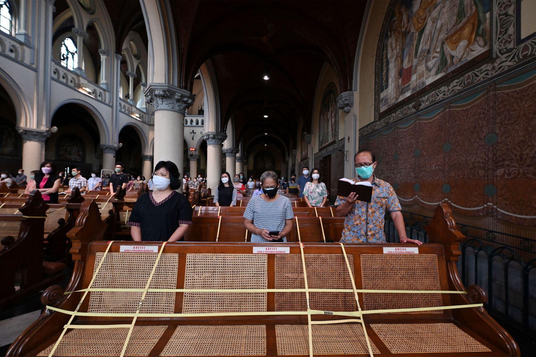 Las personas asisten a las oraciones mientras observan las medidas de prevención contra el coronavirus Covid-19, en una catedral de Yakarta. Foto: AFP