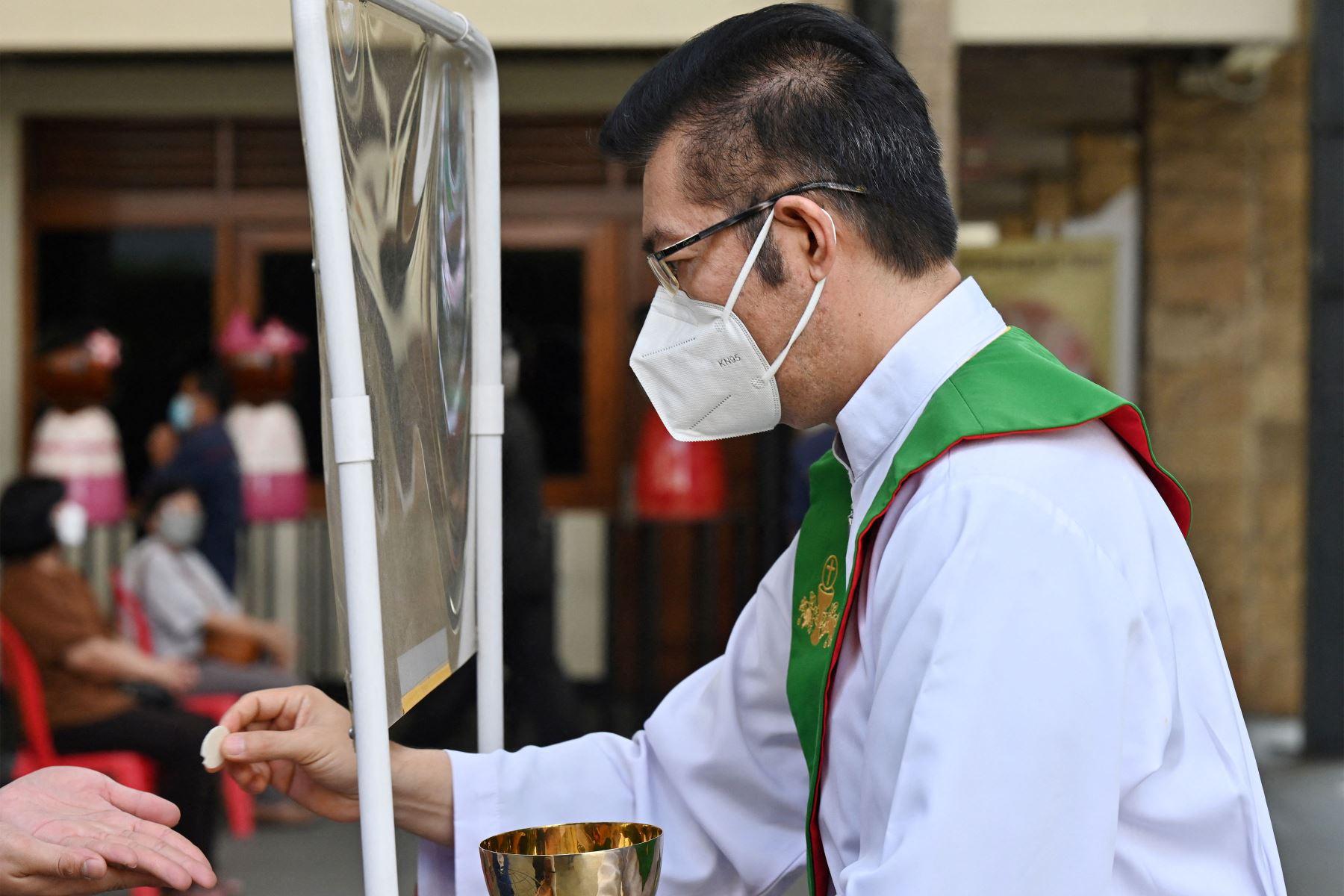 Un hombre recibe una hostia de comunión detrás de una pantalla mientras las personas asisten a las oraciones mientras observan las medidas de prevención contra el coronavirus, en una catedral de Yakarta. Foto: AFP