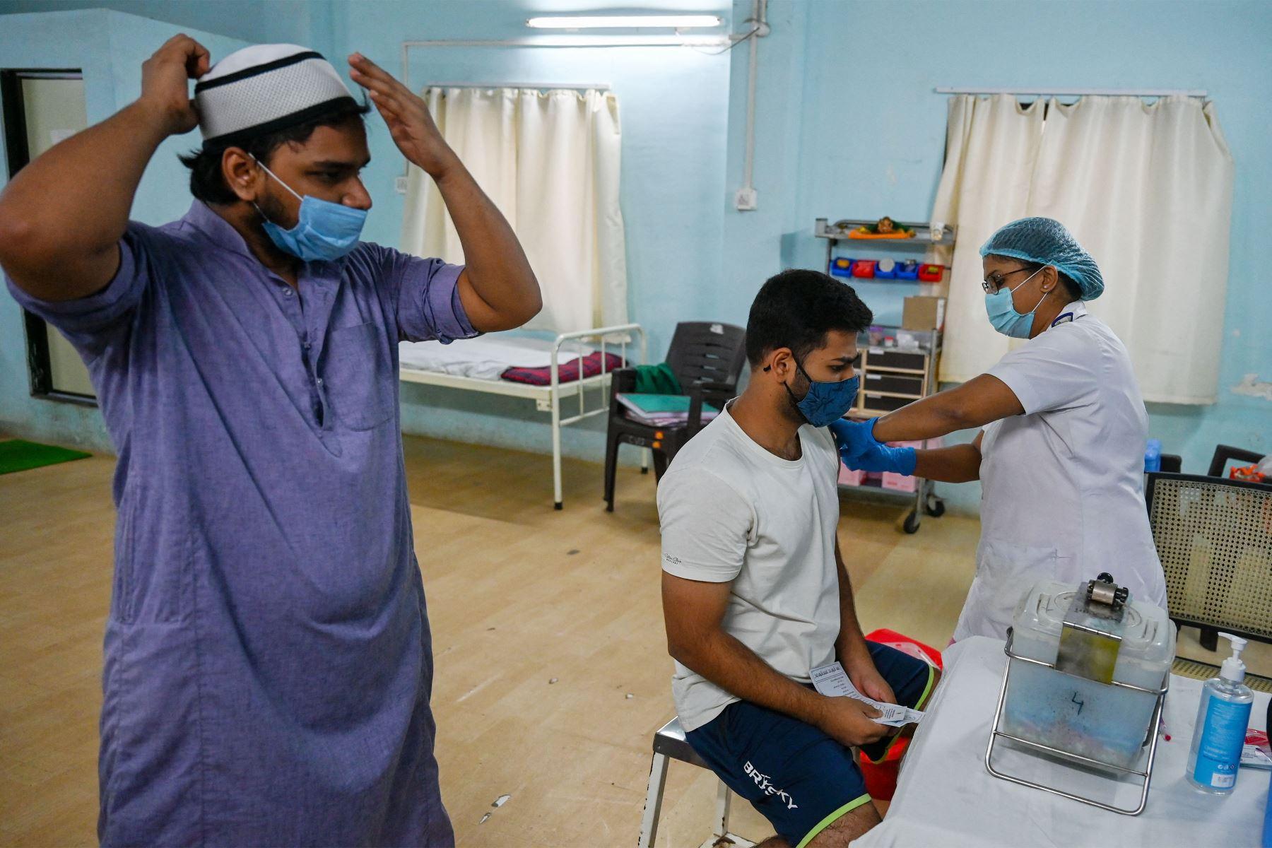 Un estudiante universitario es inoculado con una dosis de la vacuna Covishield contra el coronavirus Covid-19, en un centro de vacunación del Hospital Rajawadi en Mumbai. Foto: AFP