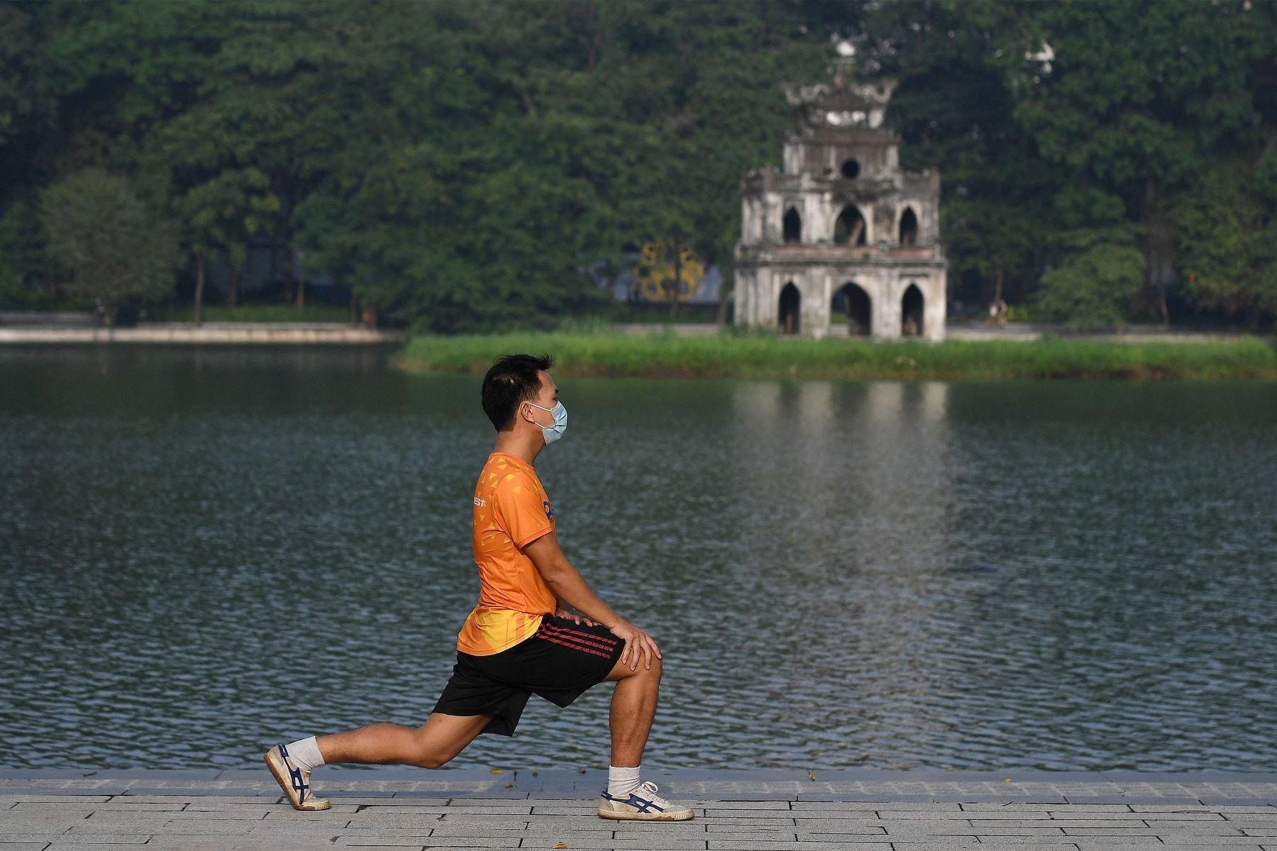 Un hombre se ejercita a lo largo del lago Hoan Kiem en Hanoi , luego de que las autoridades de la ciudad permitieran actividades deportivas al aire libre luego de la flexibilización de las restricciones del coronavirus. Foto: AFP