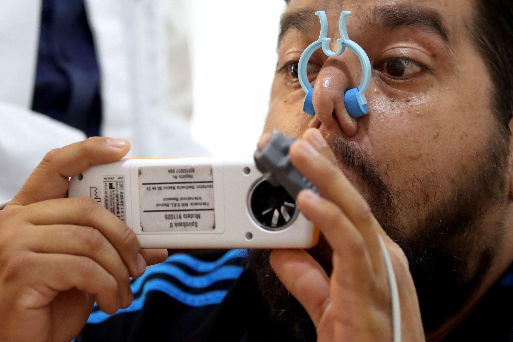 """Un hombre recibe una rehabilitación post covid-19 mediante una espirometría que mide la cantidad de aire retenido en los pulmones y la velocidad del flujo de aire durante el proceso respiratorio en la asociación """"Juntos contra el dolor"""" en Guadalajara, México. Foto: AFP"""